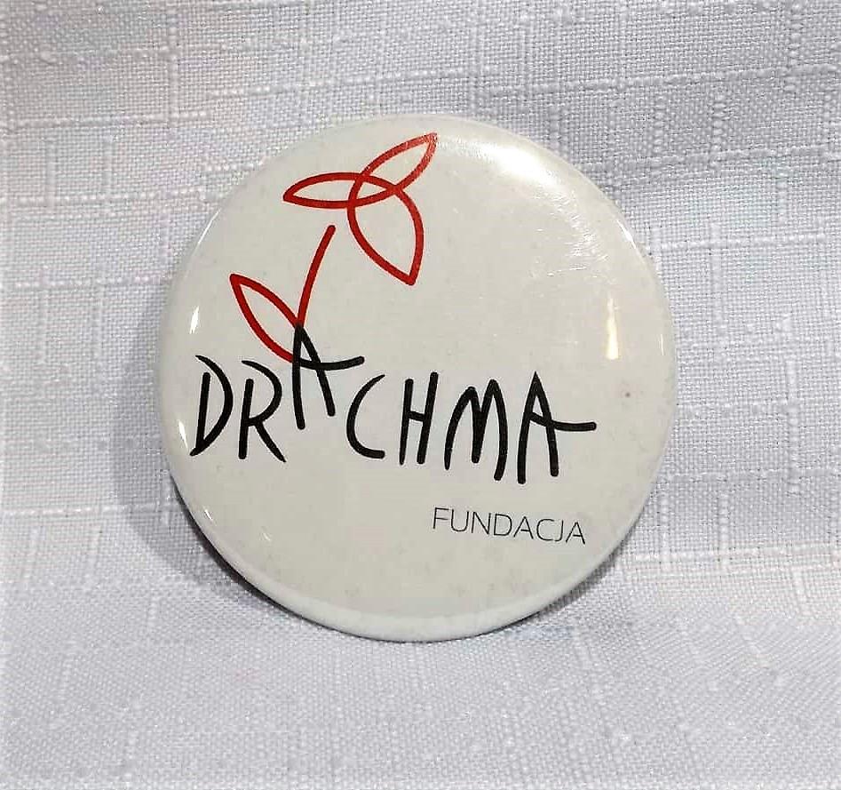Okrągła przypinka z logo Drachmy